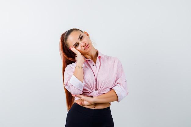 Jovem fêmea em camisa casual, inclinando a bochecha por lado e olhando confiante, vista frontal.