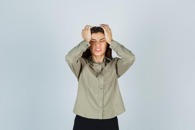 Jovem fêmea em camisa, saia, mantendo as mãos na cabeça e parecendo irritada, vista frontal.