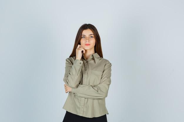 Jovem fêmea em pé na pose de pensamento de camisa, saia e parecendo sensata, vista frontal.