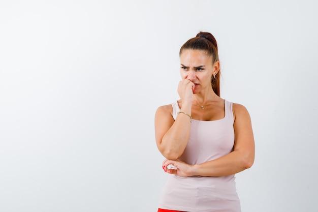 Jovem fêmea em pé na pose de pensamento na camiseta e parecendo hesitante. vista frontal.