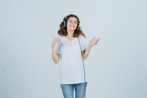 Jovem fêmea em t-shirt branca, jeans curtindo música com fones de ouvido e olhando feliz, vista frontal.