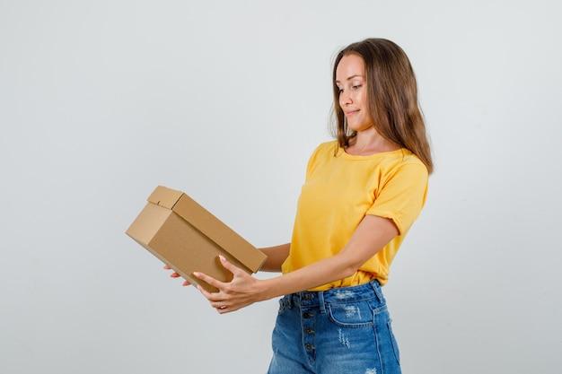 Jovem fêmea em t-shirt, calção segurando caixa de papelão e sorrindo.