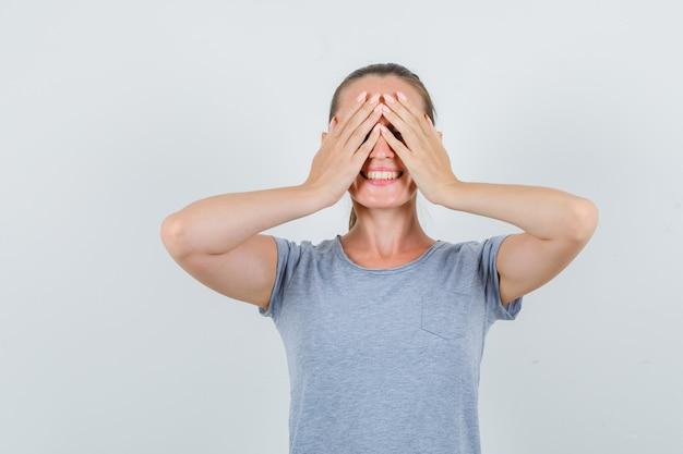 Jovem fêmea em t-shirt cinza de mãos dadas nos olhos e olhando animada, vista frontal.