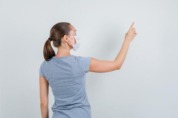 Jovem fêmea em t-shirt cinza, máscara apontando para algo acima, vista traseira.