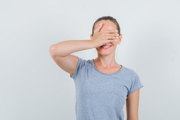 Jovem fêmea em t-shirt cinza, segurando a mão nos olhos e olhando animada, vista frontal.