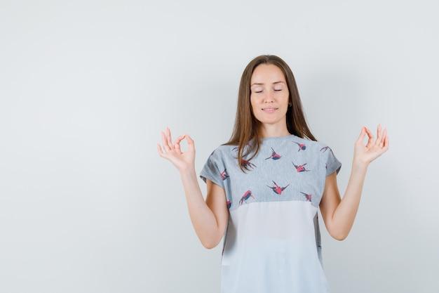 Jovem fêmea em t-shirt, fazendo meditação com os olhos fechados e olhando relaxado, vista frontal.