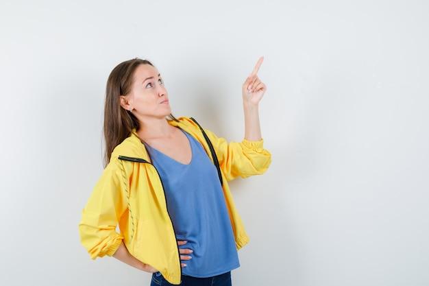 Jovem fêmea em t-shirt, jaqueta apontando para cima e olhando focada, vista frontal.