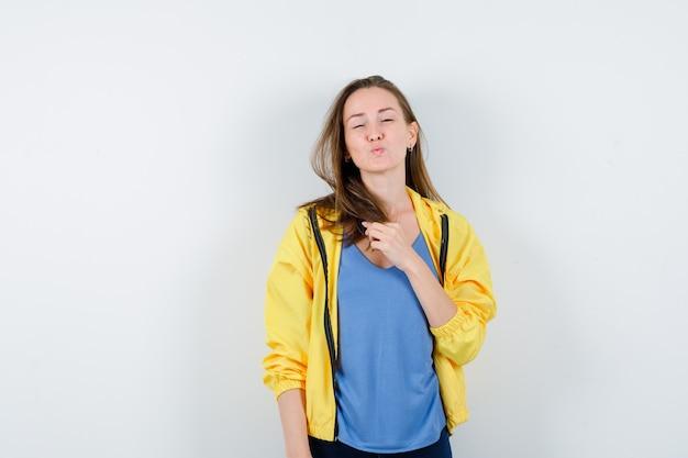 Jovem fêmea em t-shirt, jaqueta fazendo beicinho, segurando sua mecha e parecendo delicada, vista frontal.