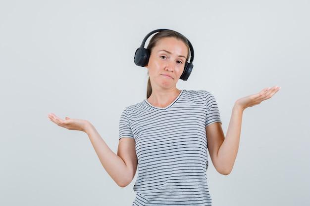 Jovem fêmea em t-shirt listrada, fones de ouvido, mostrando um gesto impotente, vista frontal.
