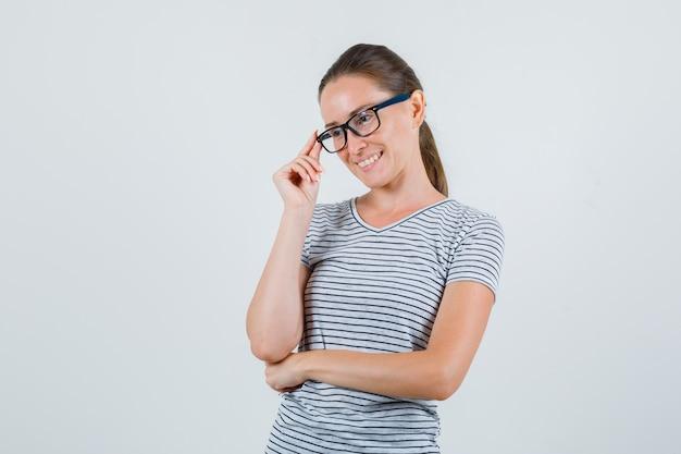 Jovem fêmea em t-shirt listrada, segurando os dedos nos óculos e olhando alegre, vista frontal.
