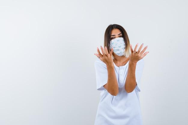 Jovem fêmea em t-shirt, máscara, mantendo as mãos de forma agressiva e olhando séria, vista frontal.