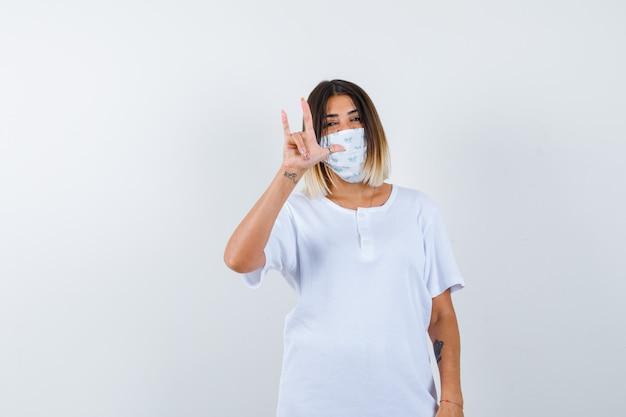 Jovem fêmea em t-shirt, máscara mostrando eu te amo gesto e olhando alegre, vista frontal.