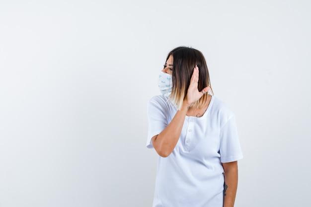 Jovem fêmea em t-shirt, máscara, segurando a mão atrás da orelha e olhando maravilhada, vista frontal.