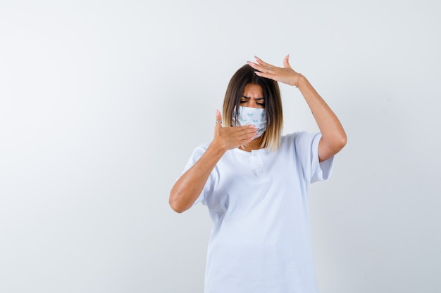 Jovem fêmea em t-shirt, máscara, segurando a mão na boca, mantendo a mão na cabeça e parecendo hesitante, vista frontal.