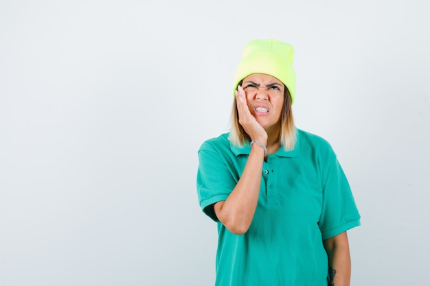 Jovem fêmea em t-shirt polo, gorro, sofrendo de dor de dente e parecendo dolorido, vista frontal.