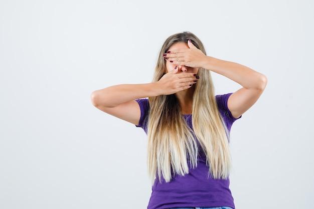 Jovem fêmea em t-shirt violeta de mãos dadas sobre os olhos e boca e olhando a vista frontal oculta.