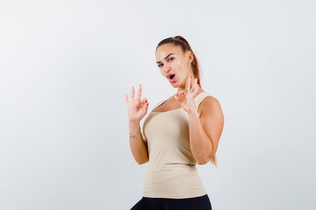 Jovem fêmea em um top bege, mostrando um gesto ok e parecendo feliz, vista frontal.
