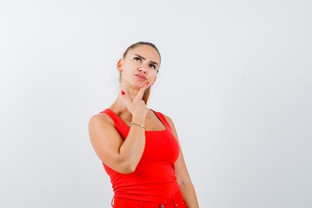 Jovem fêmea em um top vermelho, calças olhando para cima e olhando pensativa, vista frontal.