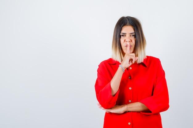 Jovem fêmea em uma camisa vermelha grande, mostrando o gesto de silêncio e olhando confiante, vista frontal.