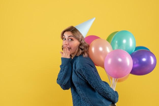 Jovem fêmea escondendo balões coloridos atrás das costas em amarelo