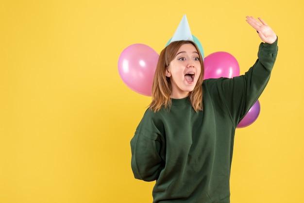 Jovem fêmea escondendo balões coloridos de frente