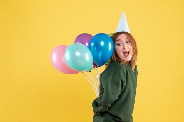 Jovem fêmea escondendo balões coloridos nas costas
