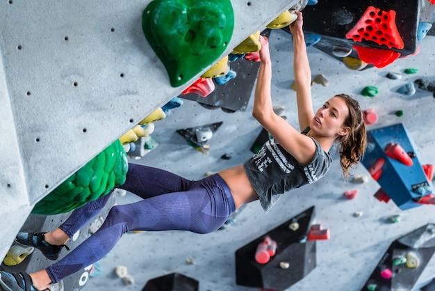 Jovem fêmea fazendo escalada