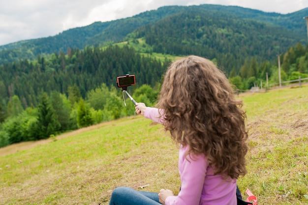 Jovem fêmea fazendo selfie no topo da colina de montanhas com vista perfeita.