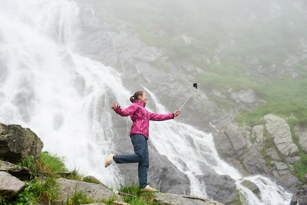 Jovem fêmea fazendo selfie posando na pedra em frente a cachoeira magnífica