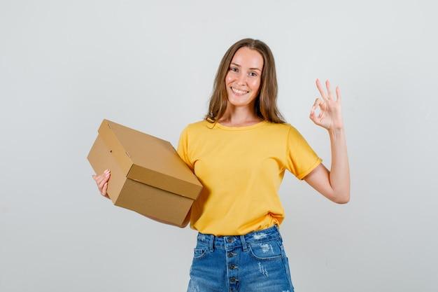 Jovem fêmea fazendo sinal de ok com caixa de papelão em t-shirt, shorts e parece feliz. vista frontal.