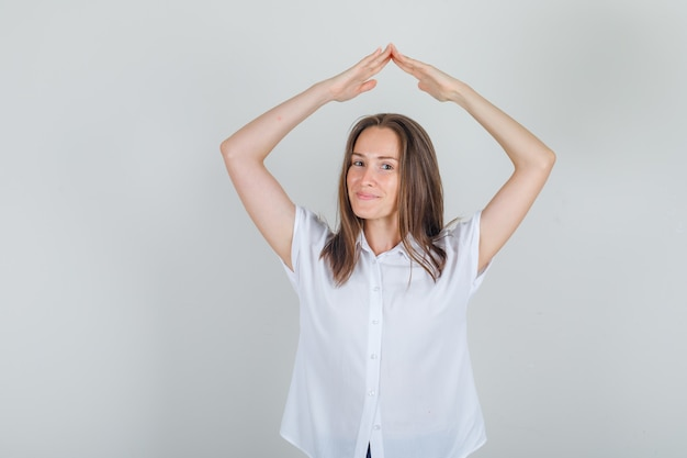 Jovem fêmea fazendo sinal de telhado de casa em uma camisa branca e parecendo alegre