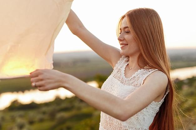Jovem fêmea fazendo um desejo e lançando a lanterna do céu de papel