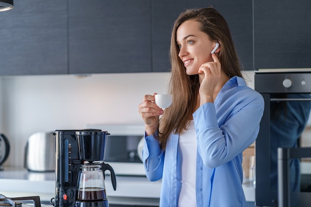 Jovem fêmea feliz com fones de ouvido sem fio brancos, ouvir música e áudio livro durante o café fresco e aromático na cozinha em casa. pessoas móveis modernas