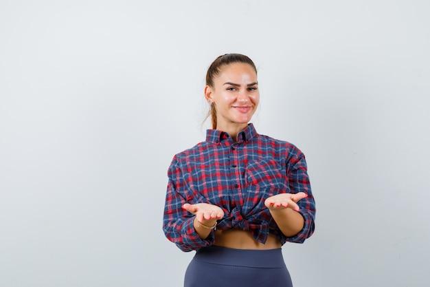 Jovem fêmea fingindo segurar algo em camisa quadriculada, calças e parecendo feliz, vista frontal.