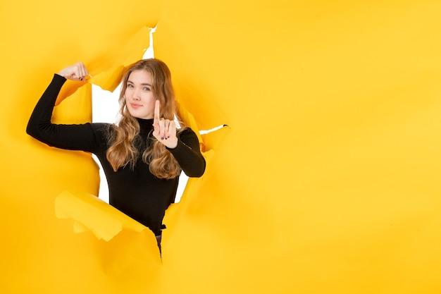 Jovem fêmea flexionando-se na parede amarela rasgada de frente