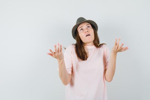 Jovem fêmea levantando as mãos de forma questionadora em t-shirt rosa, vista frontal do chapéu.