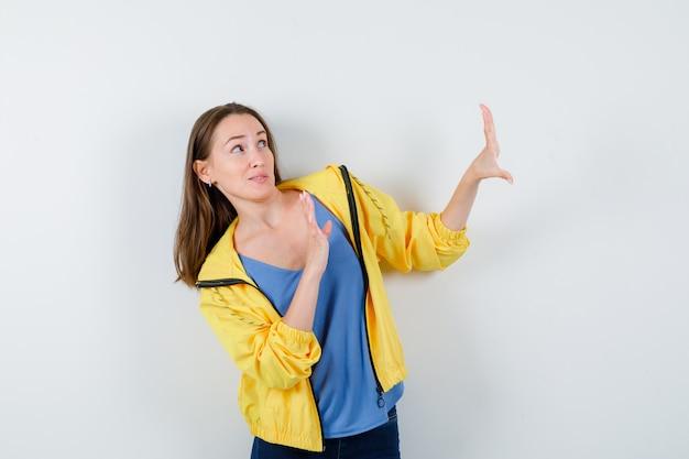 Jovem fêmea levantando as mãos para se defender em t-shirt, jaqueta e parecendo assustada, vista frontal.
