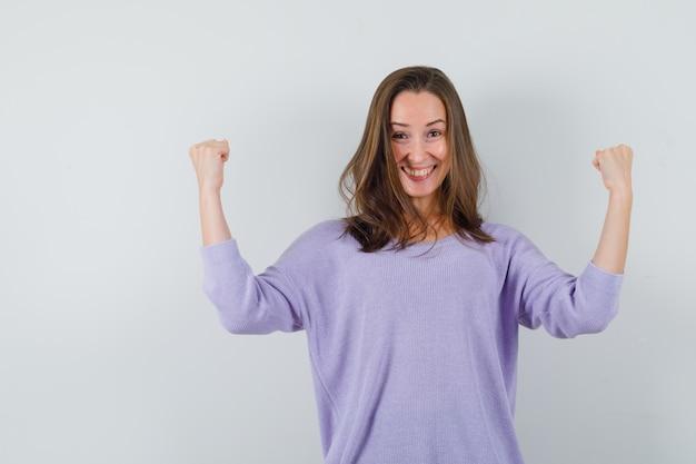 Jovem fêmea levantando os braços enquanto mostra o gesto do vencedor na blusa lilás e parece feliz. vista frontal.