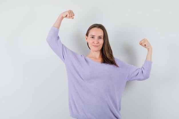 Jovem fêmea levantando os braços enquanto mostra os músculos do braço em uma blusa lilás e parece poderosa. vista frontal.