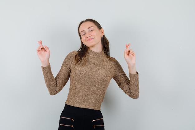 Jovem fêmea levantando os dedos cruzados na blusa dourada e olhando ansiosa, vista frontal.