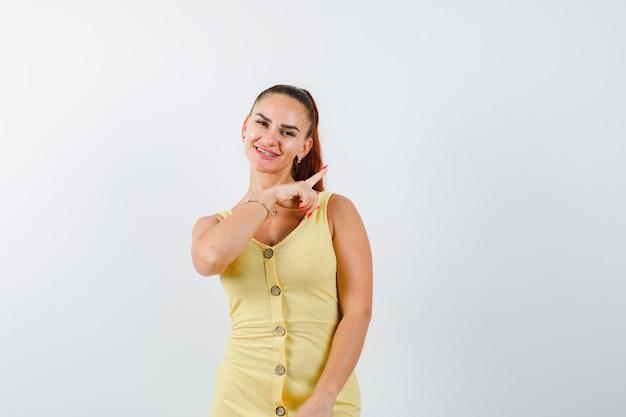 Jovem fêmea linda apontando para o canto superior direito do vestido e olhando alegre, vista frontal.
