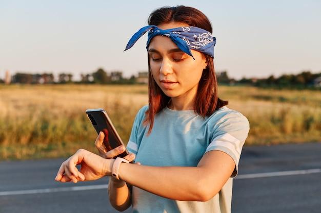Jovem fêmea linda consertando a braçadeira antes de treinar com o pôr do sol no fundo. garota atraente com preparação para o treino, usando faixa de cabelo e camiseta estilo casual.