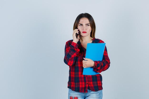 Jovem fêmea linda em camisa casual, jeans segurando uma pasta enquanto falava no telefone, olhando para longe e olhando mal-humorada, vista frontal.
