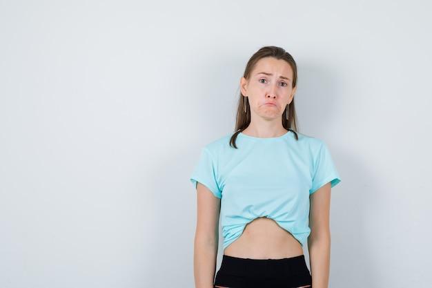 Jovem fêmea linda em t-shirt, olhando para a câmera e olhando mal-humorada, vista frontal.