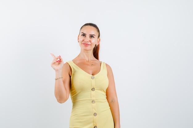 Jovem fêmea linda em um vestido apontando para o canto superior esquerdo e olhando alegre, vista frontal.