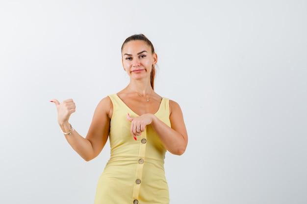 Jovem fêmea linda em um vestido apontando para o lado com os polegares e parecendo decepcionada, vista frontal.