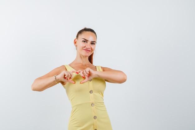 Jovem fêmea linda em um vestido mostrando um gesto de coração e olhando feliz, vista frontal.