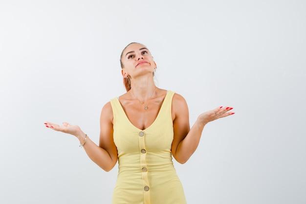 Jovem fêmea linda em um vestido mostrando um gesto de impotência enquanto olha para cima e parece pensativa, vista frontal.