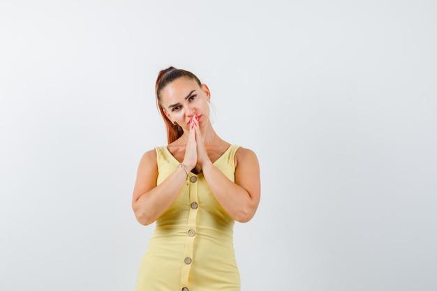 Jovem fêmea linda num vestido de mãos dadas em gesto de oração e olhando pensativa, vista frontal.