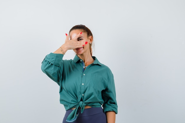 Jovem fêmea linda olhando por entre os dedos na camisa verde e parecendo alegre. vista frontal.